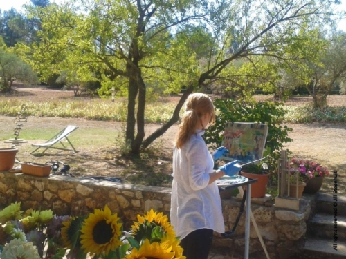 A workshopper paints under the almond tree in Jill's garden