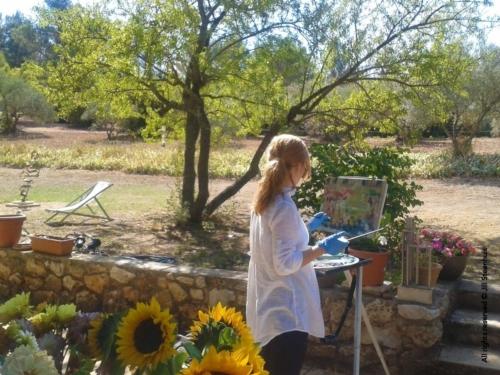A workshopper paints under the almond tree in Jill's garden